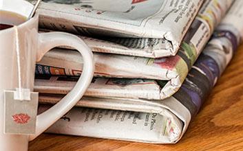 Apilado de periódicos con taza